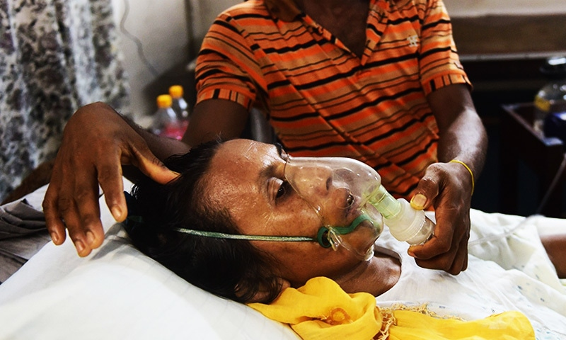 Rohingya Muslim refugee Sadekun Nahar, 50, is tended to by her son as she is treated in a hospital.— AFP