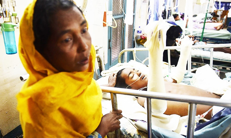 In this picture Rashida Begum stands next to her son Azizul Haque, 15, as he is treated after being injured by a landmine while crossing from Myanmar to Bangladesh.—AFP