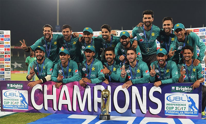 Pakistani cricketers pose for a photograph with the Independence Cup trophy after winning the third and final T20I against the visiting World XI at the Gaddafi Cricket Stadium in Lahore. ─ AFP