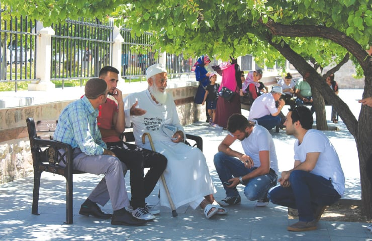 A teacher imparts spiritual wisdom to youth, under a tree near Mevlana Rumi's sarcophagus
