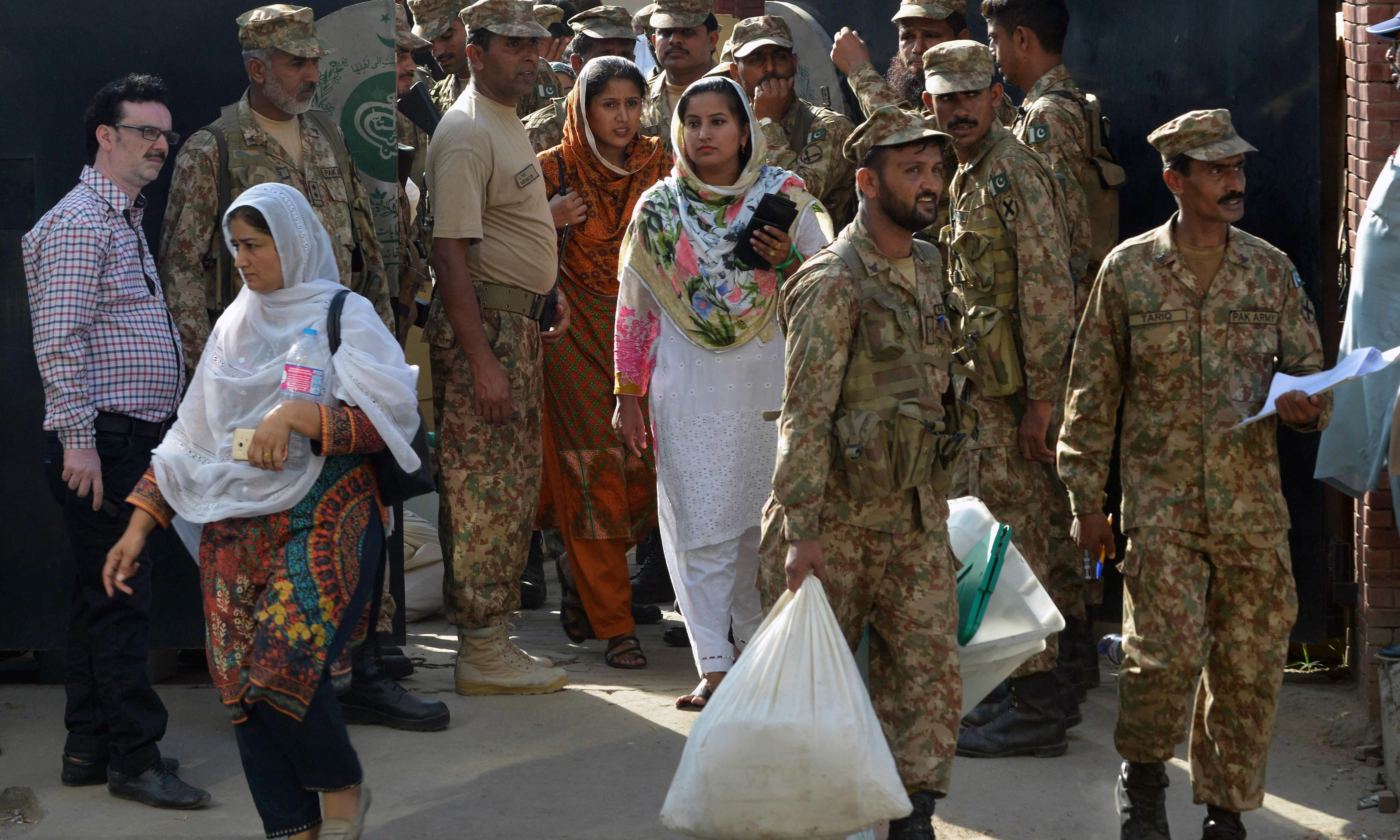 Soldiers help polling officers carry election materials received from the ECP office in Lahore. —AFP