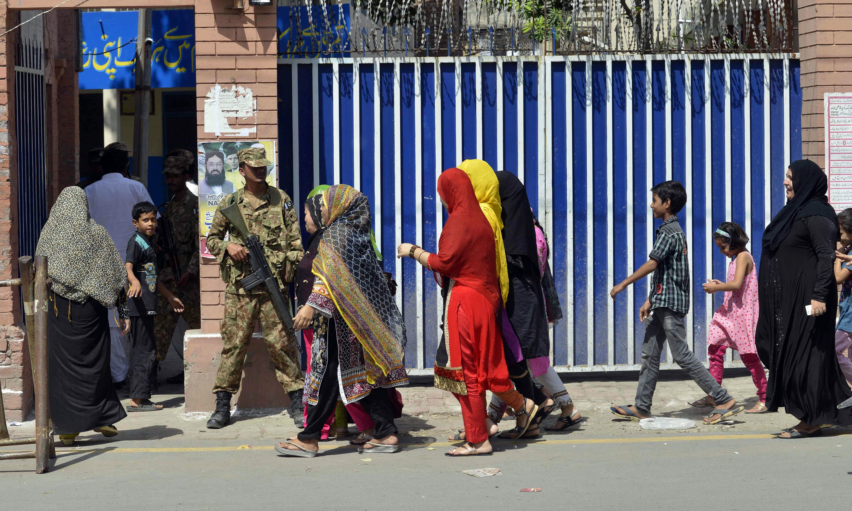 Security personnel stand guard as voters queue to cast their ballots in a by-election in Lahore. —AFP