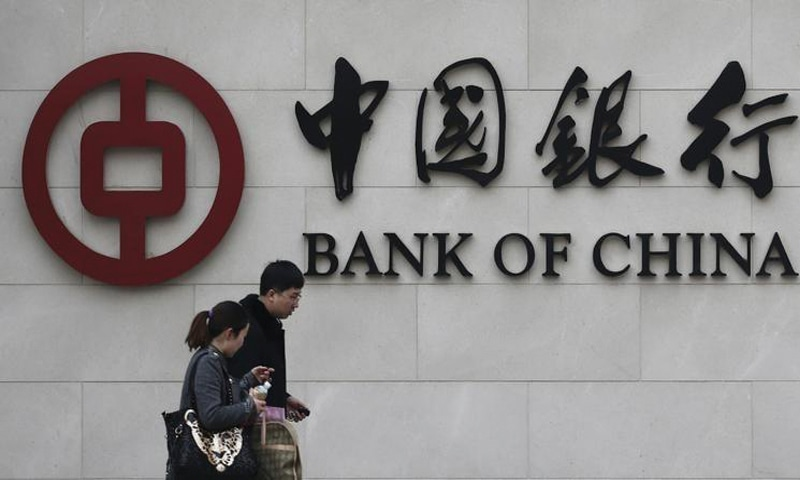 BEIJING: In this file photo, pedestrians walk past a Bank of China sign at its branch.— Reuters