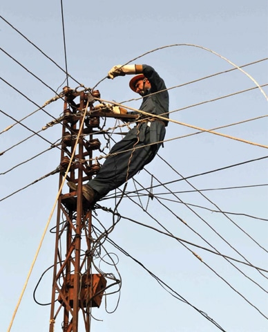 SARGODHA: In this file photo, a worker is fixing electric line at Sashan Road.—APP