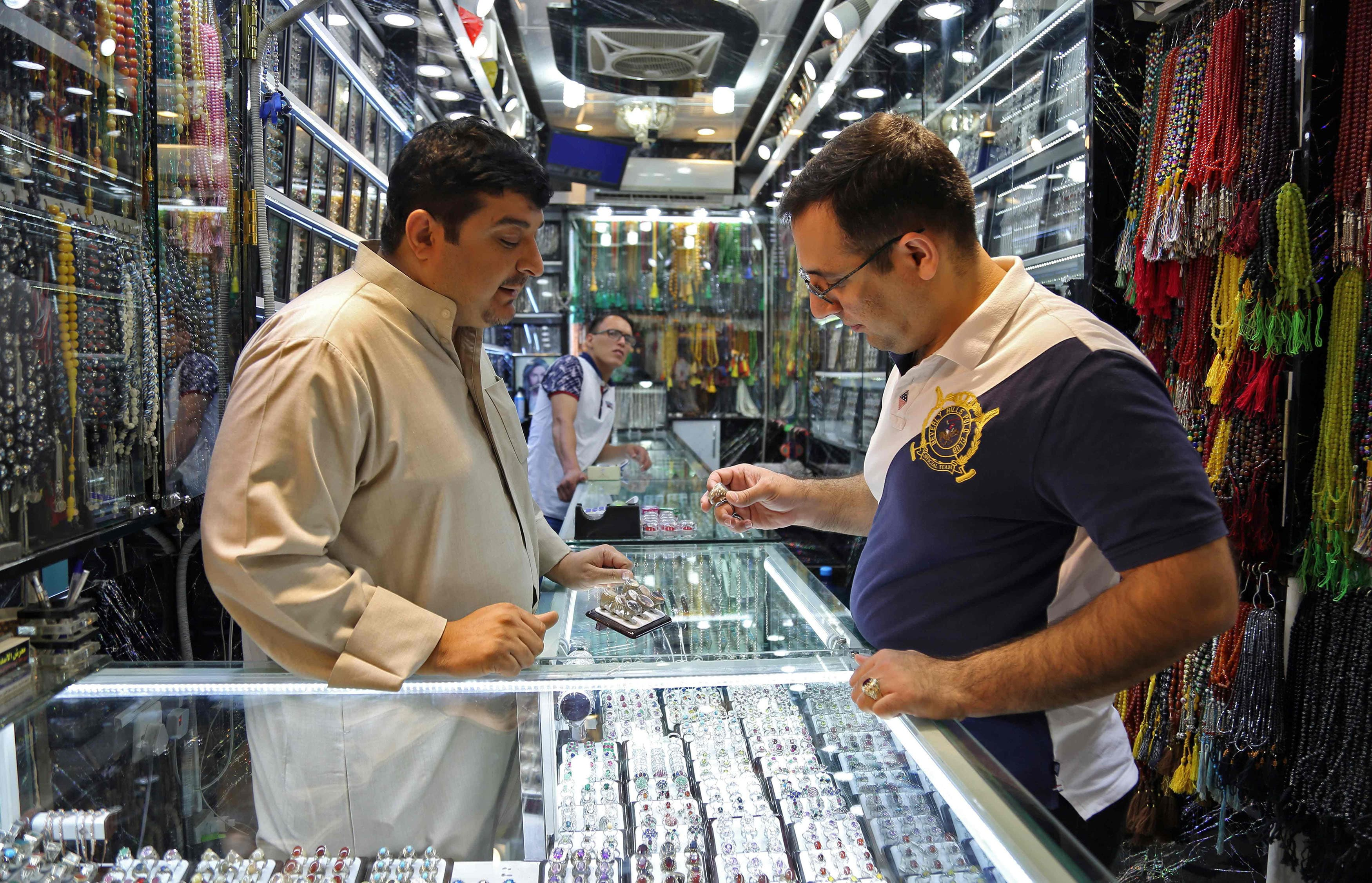 A man browses for rings at a jeweller's in the main market of Iraq's holy city of Najaf on September 13, 2017. Strategically located facing the golden gate of the mausoleum, the Shiite religious calendar controls the life of the market's gemstone traders, for whom boom times on major religious ceremonies are a boon as the increase in demand sends the most prized rings into the thousands of dollars bracket. / AFP PHOTO / Haidar HAMDANI — AFP or licensors