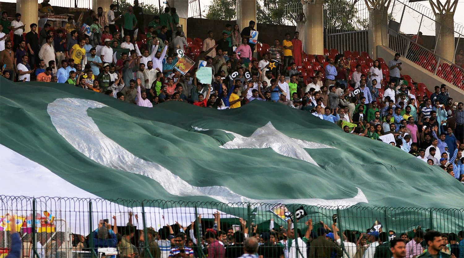Pakistani spectators display a huge national flag at the Gaddafi Cricket Stadium in Lahore before the start of the third and final match between the World XI and Pakistan. -AFP