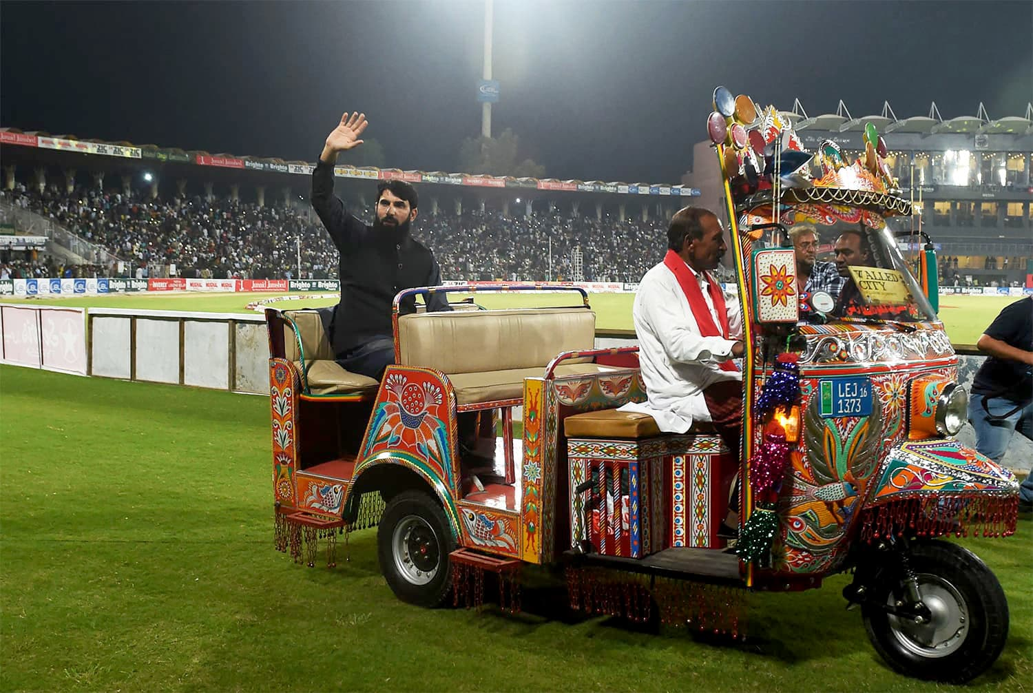 Pakistani former captain Misbah ul Haq (L) rides on an auto-rickshaw as he waves to the crowd. -AFP