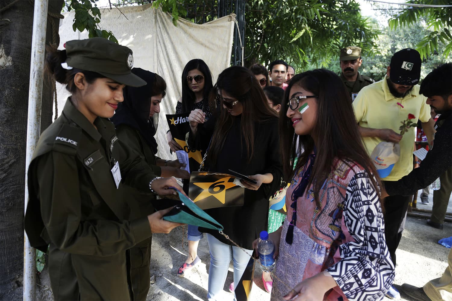 Pakistani police officers check cricket spectators arriving to watch the final match between Pakistan and World XI at Gaddafi stadium in Lahore. -AP