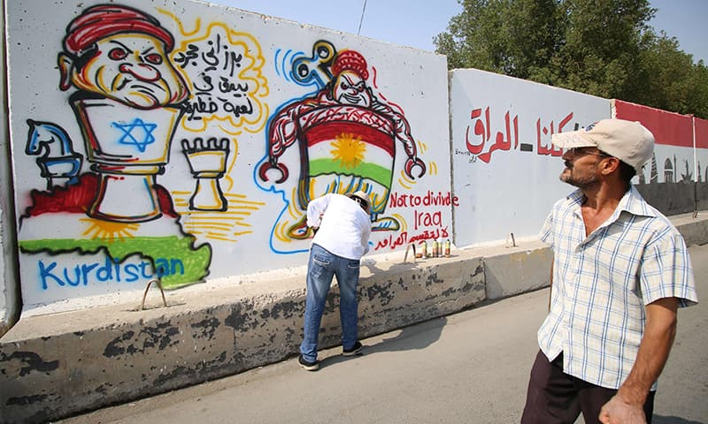 """In the southern Iraqi city of Basra, Iraqi cartoonist Arkan Al-Bahadly using a spray-paint cannister to draw a graffiti on a wall critical of the Kurdistan independence referendum, depicting Kurdish regional president Massoud Barzani as a pawn bearing the star of David, with writing in Arabic reading: """"Barzani is just a pawn in a dangerous game.""""─AFP"""