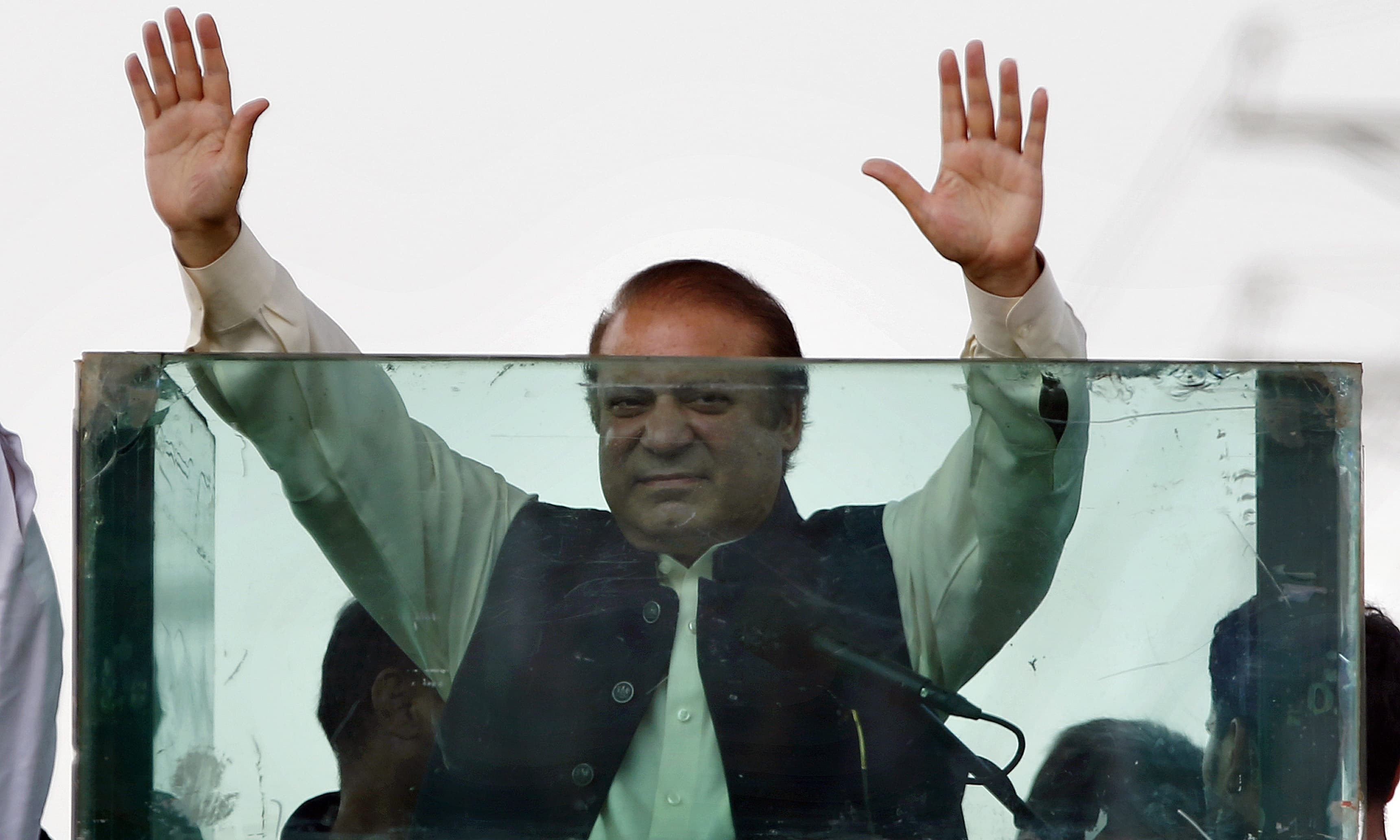 Nawaz Sharif raises his hands to respond to his supporters during a rally in Muridke on August 12.— AP/File