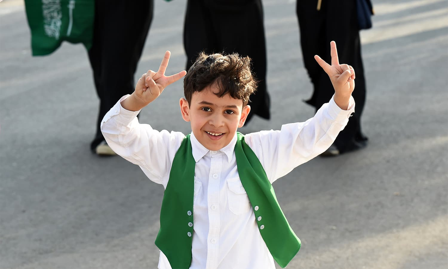A Saudi boy flashes the victory gesture with both his hands as he arrives outside a stadium to attend an event in the capital Riyadh. — AFP