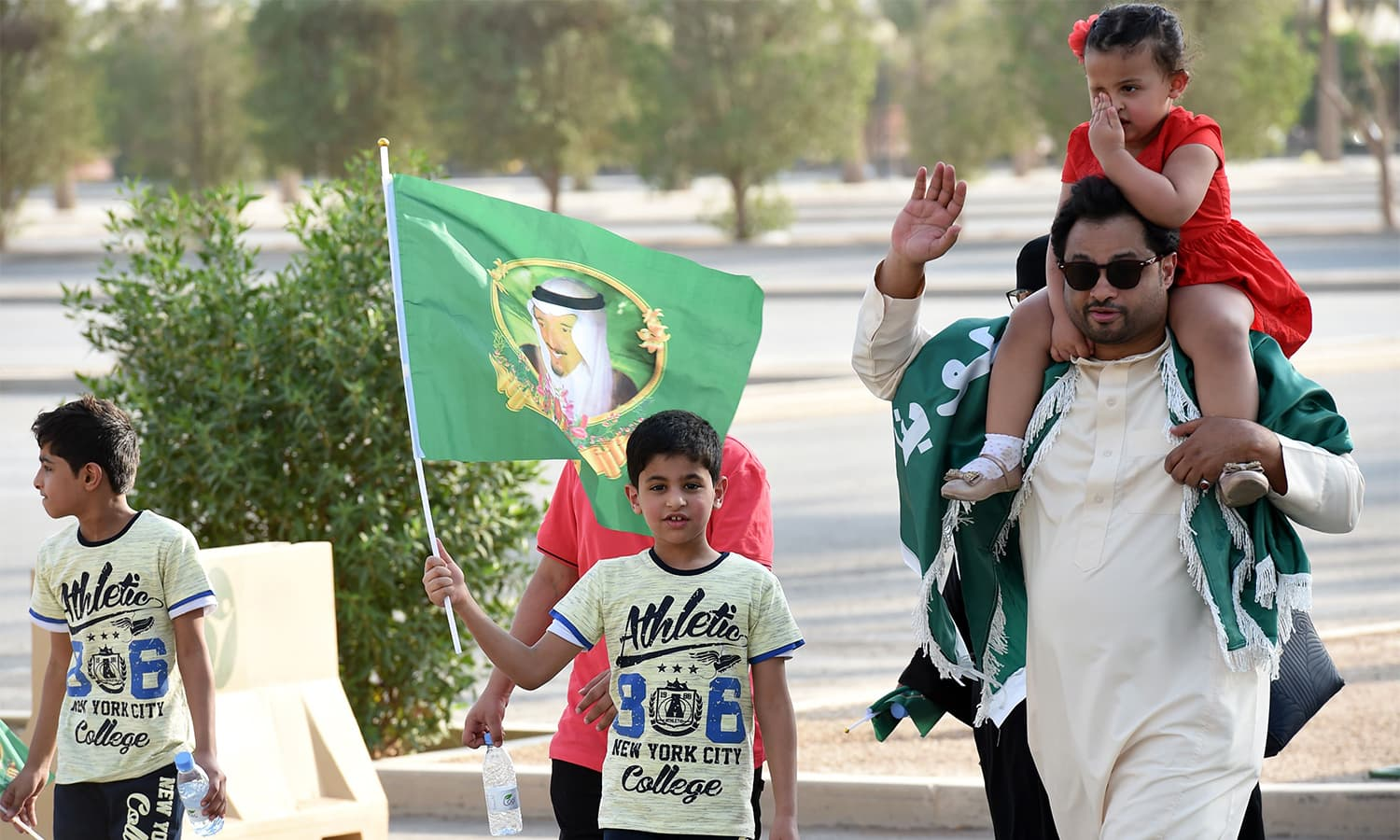 A Saudi boy waves a flag bearing the image of the king as he arrives with his family outside a stadium to attend an event in the capital Riyadh. — AFP