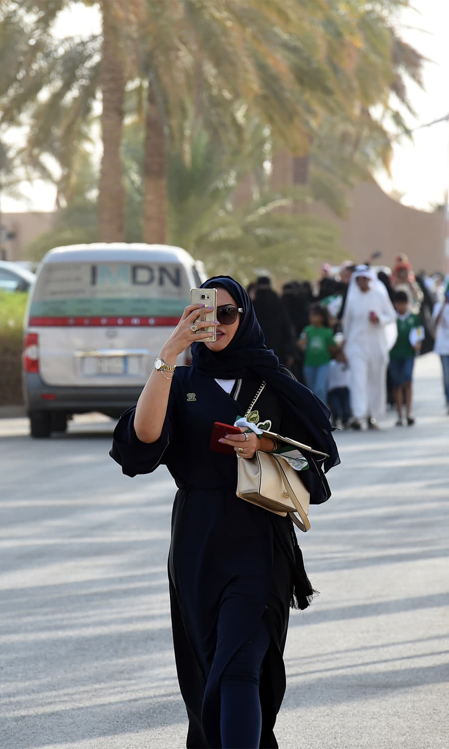 A Saudi woman uses her cell phone to take a picture as she arrives outside a stadium to attend an event in the capital Riyadh. — AFP