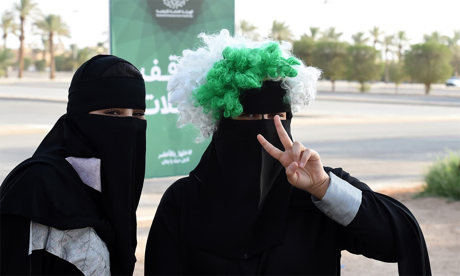 A Saudi woman flashes the victory gesture while wearing a coloured wig above her head-dress, as she arrives outside a stadium to attend an event in the capital Riyadh. — AFP