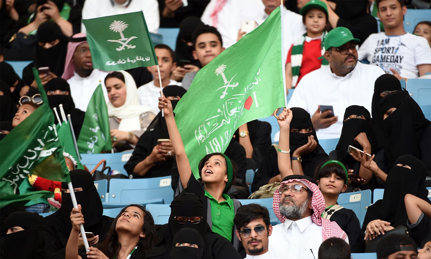 "A Saudi boy waves a flag bearing the kingdom's emblem and with a caption reading in Arabic ""the nation is in our hearts"", as he sits with other families in a stadium to attend an event in the capital Riyadh. — AFP"