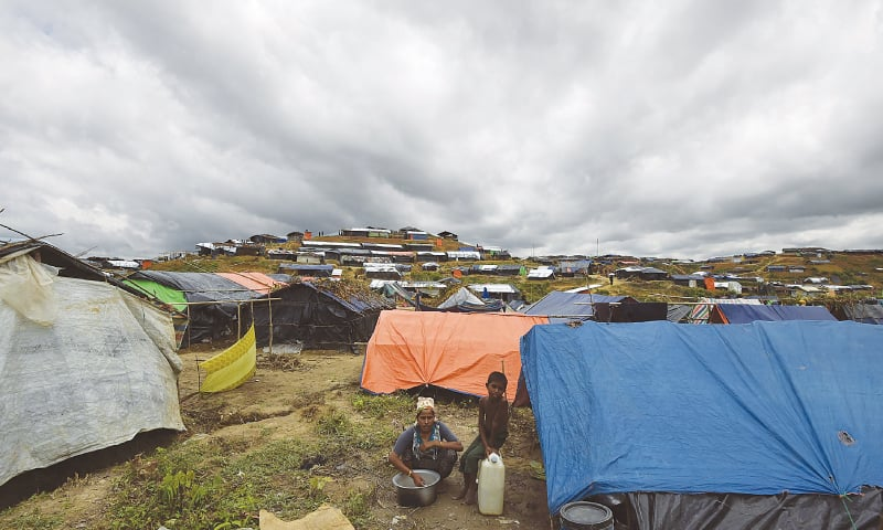 Rohingya refugees sitting by their tents at the Kutupalong refugee camp in Bangladesh on Sunday.—AFP