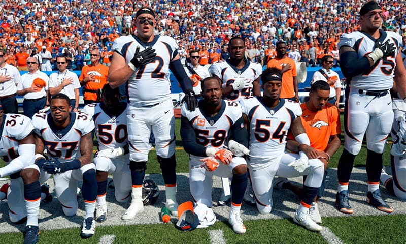 NFL players kneel in protest after Trump urges fans to boycott games