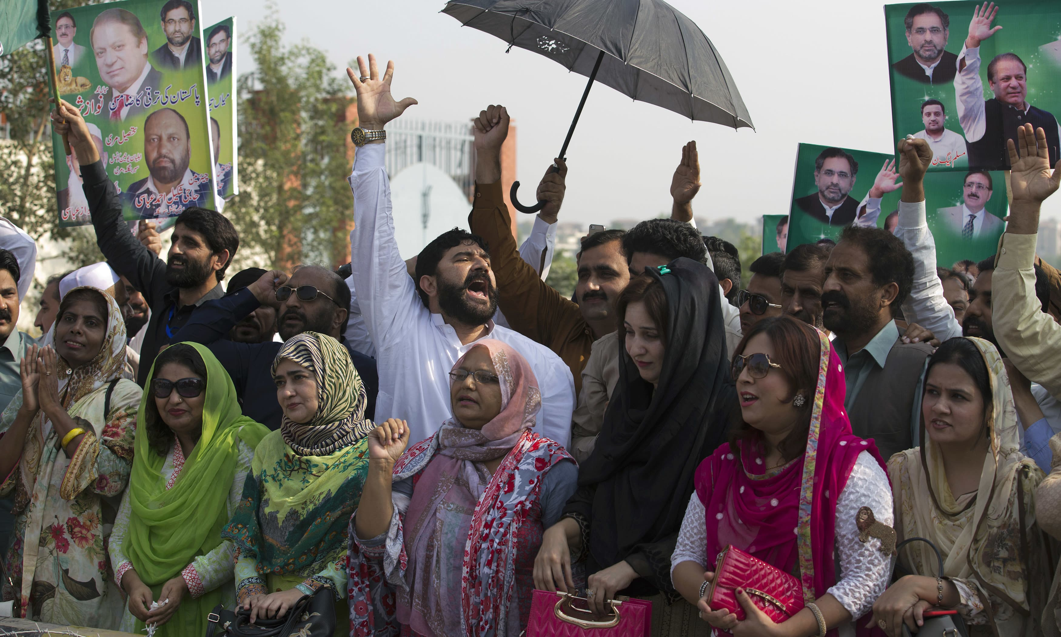 PML-N supporters shout slogans to cheer Nawaz Sharif outside the NAB court in Islamabad. —AP