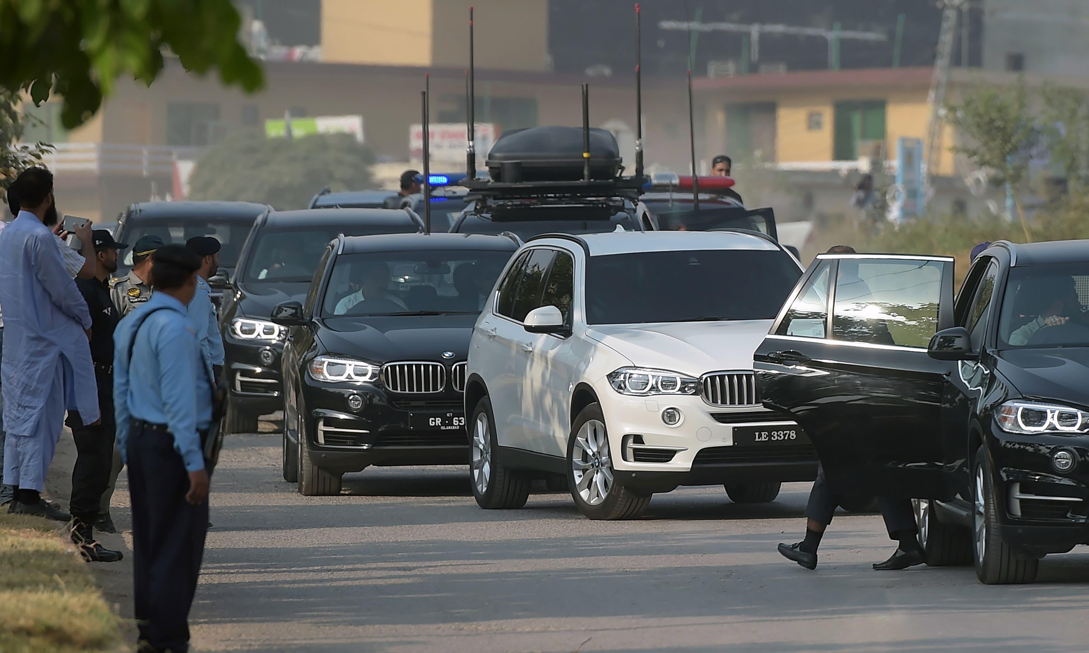 Security vehicles escort a white car carrying Nawaz Sharif. —AFP