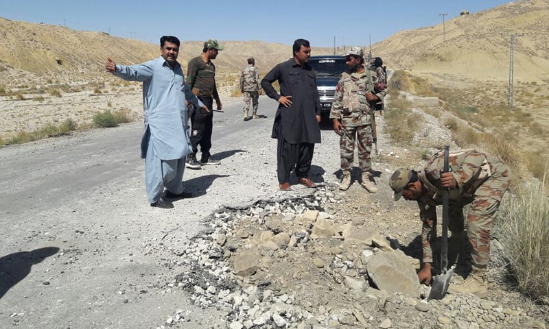 Security forces examine the blast site.— DawnNews