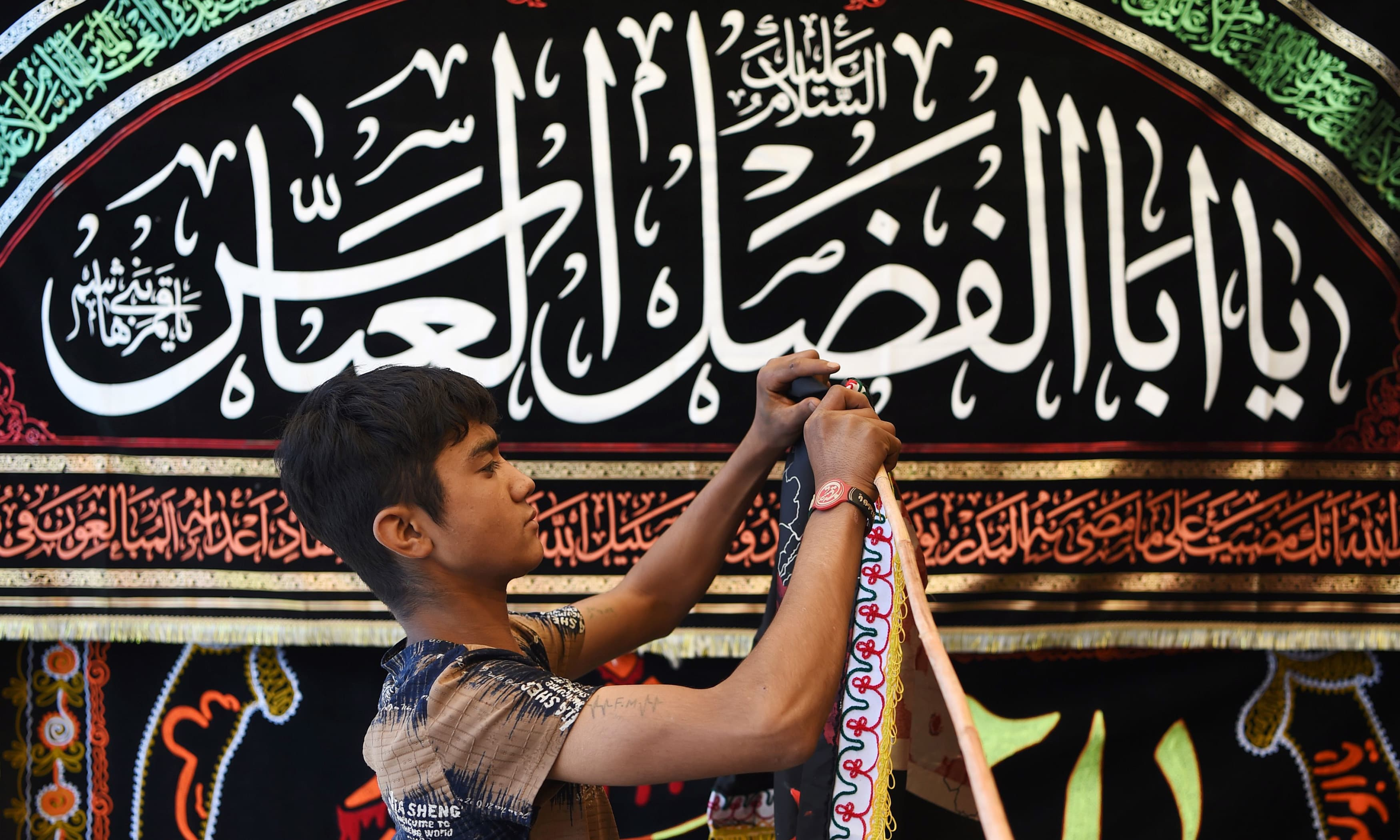 A boy displays religious flags ahead of Ashura along a roadside in Kabul. —AFP