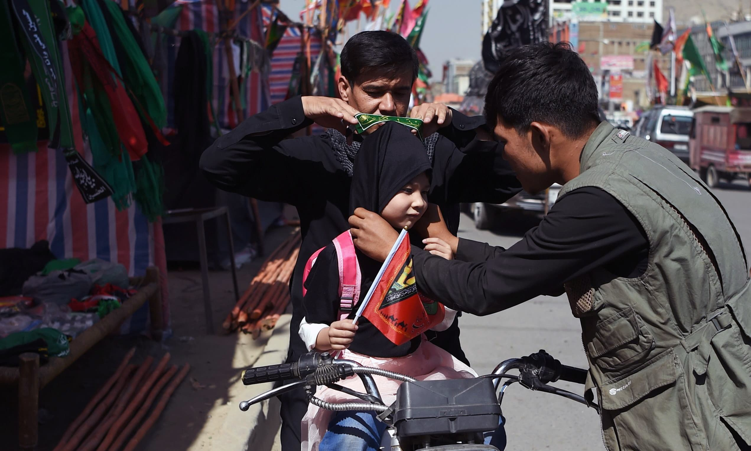 A man adjusts a scarf on a child ahead of Ashura along a roadside in Kabul. —AFP