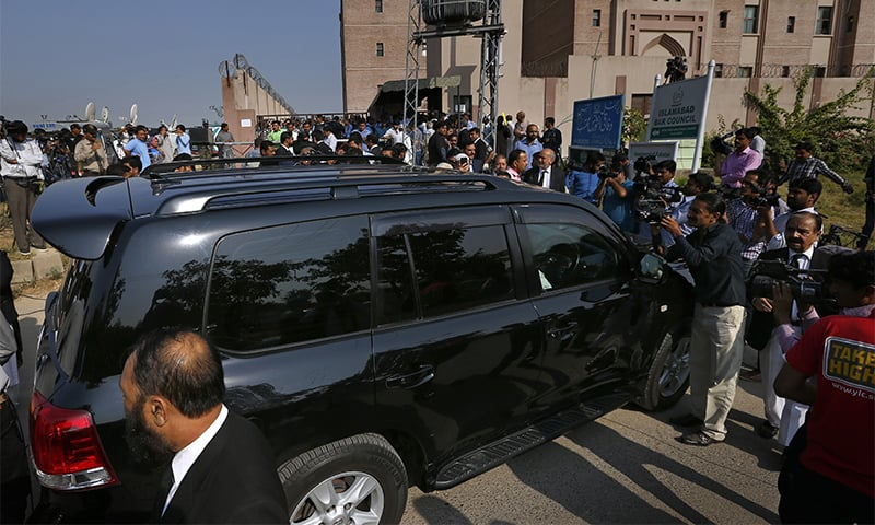 A vehicle carrying Ishaq Dar is surrounded by members of media upon his arrival to appear in an accountability court.— AP