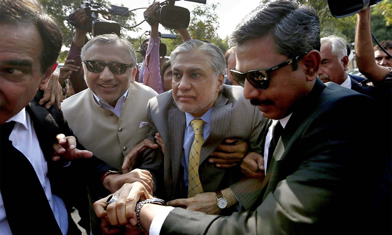 Finance Minister Ishaq Dar, centre, arrives with his lawyer Amjad Pervez, right, to appear in an accountability court in Islamabad on Wednesday.— AP