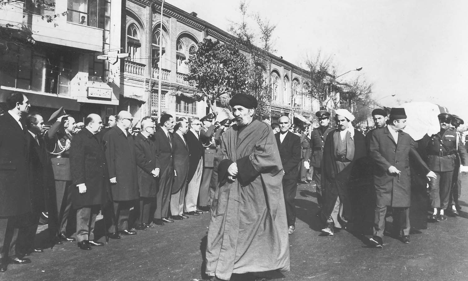 Iranian Foreign Minister Ardeshir Zahedi (extreme left) and Prime Minister Amir-Abbas Hoveyda (fourth from left) standing to join in the funeral procession of President Iskander Mirza . | Photo: The Iskander Mirza Family Collection, Karachi