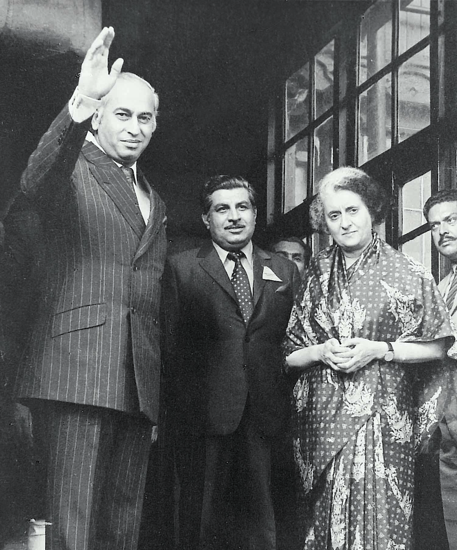 President Zulfikar Ali Bhutto waves towards the cameras as Prime Minister Indira Gandhi looks on during talks that led to the signing of the Simla Agreement on July 2, 1972. Standing in the middle is Ghulam Mustafa Jatoi. | Photo: Dawn / White Star Archives