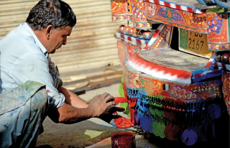 A worker in Pirwadhai paints small bells at the base of a public transport vehicle.