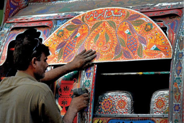 Mohammad Saleem fixes colourful stickers and reflectors onto a vehicle. A taj, or crown, is fixed on the vehicle's roof. — Photos by Mohammad Asim