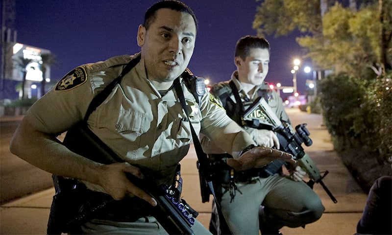 Police officers advise people to take cover near the scene of a shooting near the Mandalay Bay resort and casino on the Las Vegas Strip. ─ AP