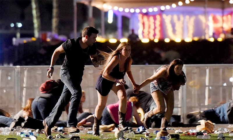 People run from the Route 91 Harvest country music festival after gunfire was heard. ─ AP