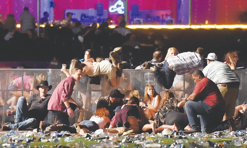 LAS VEGAS: People roll over a wall in a scramble for shelter after a gunman started shooting at a music festival on Sunday night.—AFP