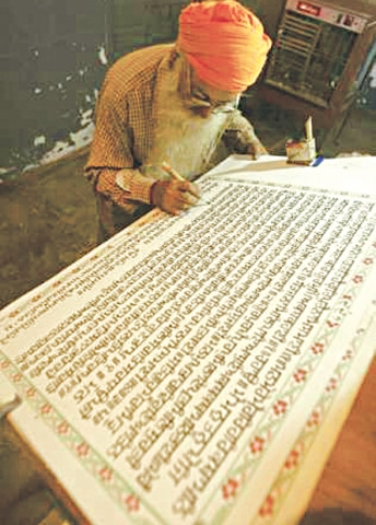 A scribe copies the Guru Granth Sahib by hand in the northern Indian city of Amritsar | Reuters