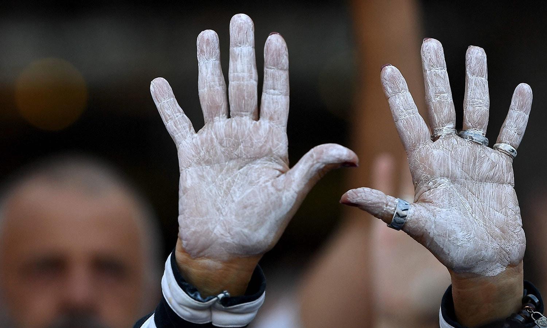 مظاہرین نے ہاتھوں میں سفید رنگ لگا کر کیٹلونیا کی اسپین کے ساتھ رہنے کے لیے مذاکرات کا مطالبہ کیا—فوٹو: اے ایف پی