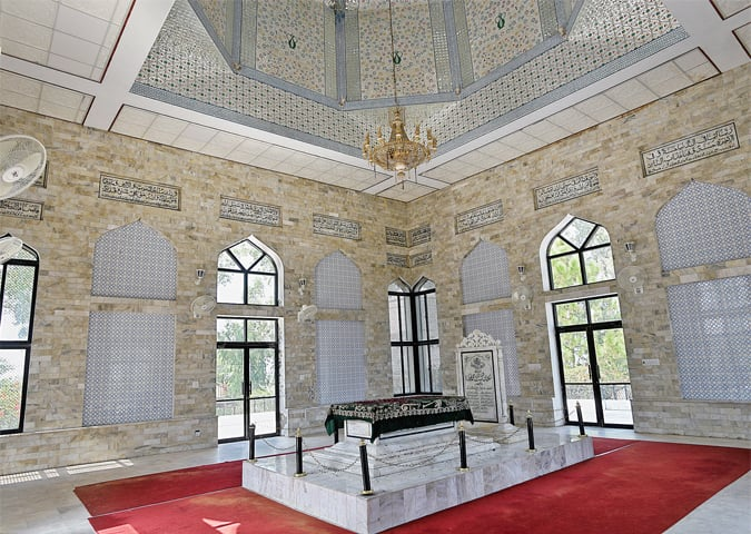 The interior of the mausoleum and the grave of Sultan Mohammad Ghori. White marble has been used on the walls and the roof is decorated with minakari.