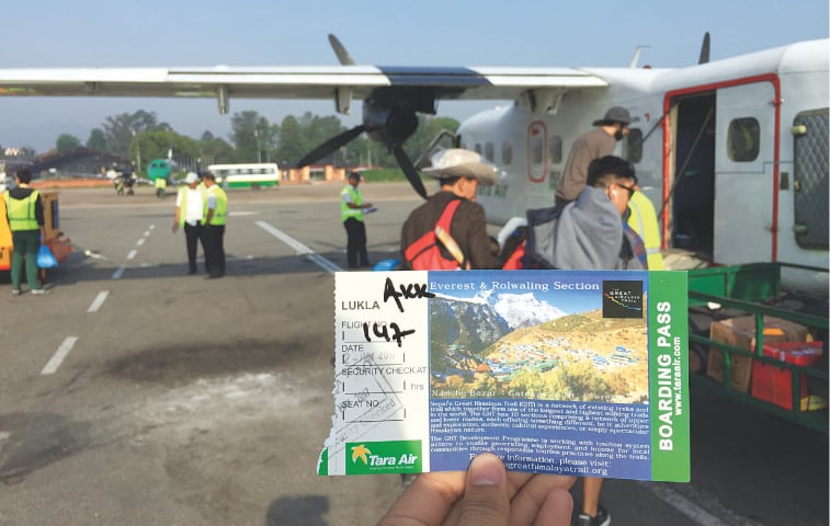 The boarding pass of the Kathmandu-Lukla flight, which looks like a postcard, with the tiny plane in the background