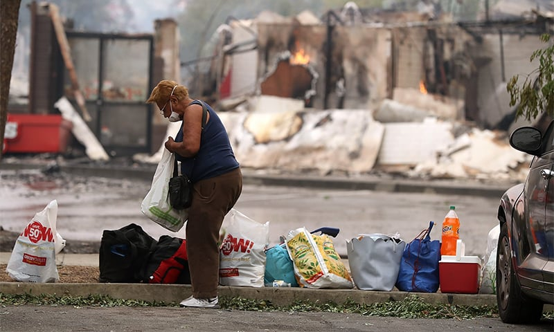 A resident goes through personal belongings in a parking lot next to a fire damaged Arby's restaurant in Santa Rosa, California.— AFP