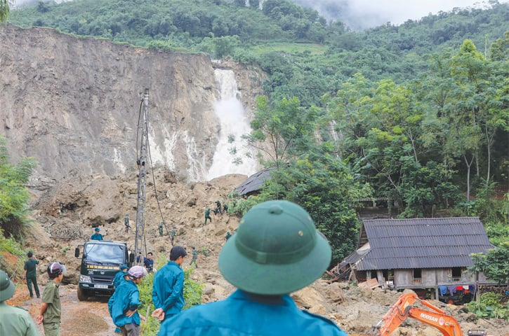 Rescuers search for bodies of victims at the site of a landslide where 18 people from four families were killed in on Thursday.—AFP