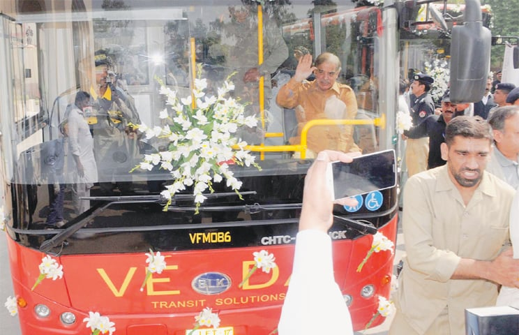 Punjab Chief Minister Shahbaz Sharif acknowledges the slogans of supporters after inaugurating the feeder bus service on Thursday.—INP