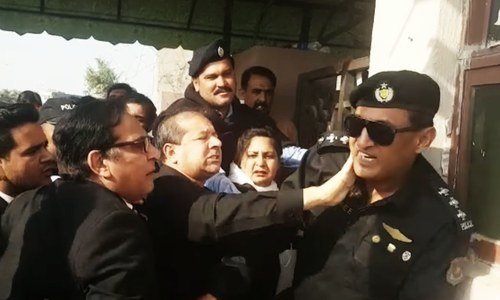 A lawyer hits a police official trying to keep the crowd from entering the court. — DawnNews