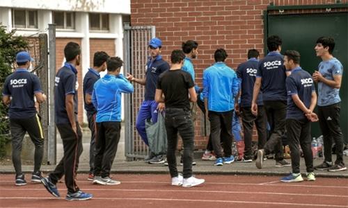 Pakistani and Afghan migrants wear shirts of their cricket club Saint-Omer Cricket Club Stars (Soccs). — AFP
