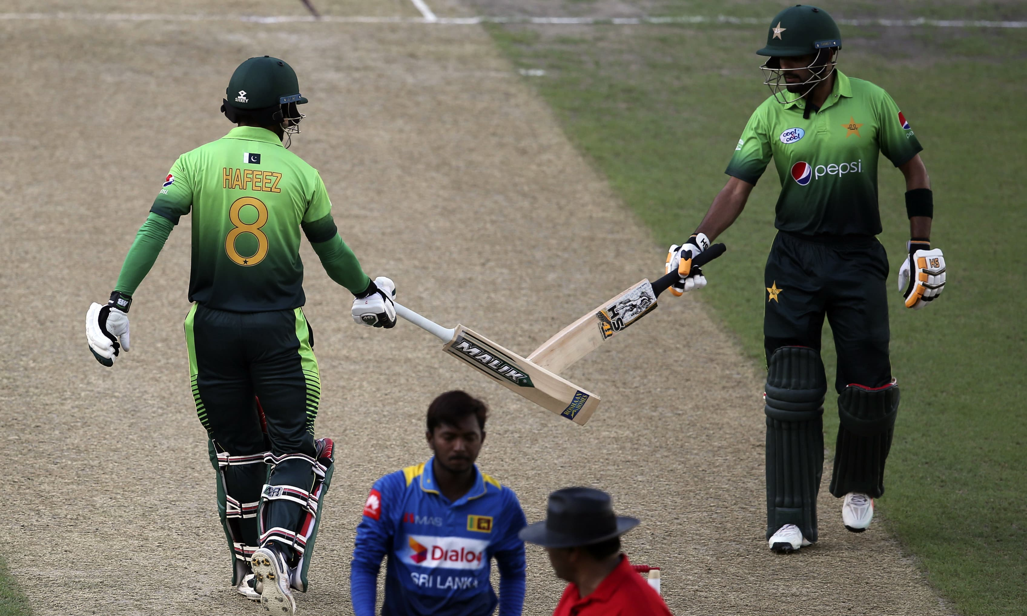 Mohammad Hafeez and Babar Azam touch their their bats during their first ODI cricket match against Sri Lanka in Dubai. —AP