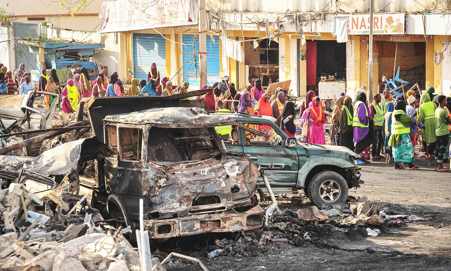 People gather near burnt vehicles a day after a truck bomb exploded in the centre of Mogadishu.─AFP