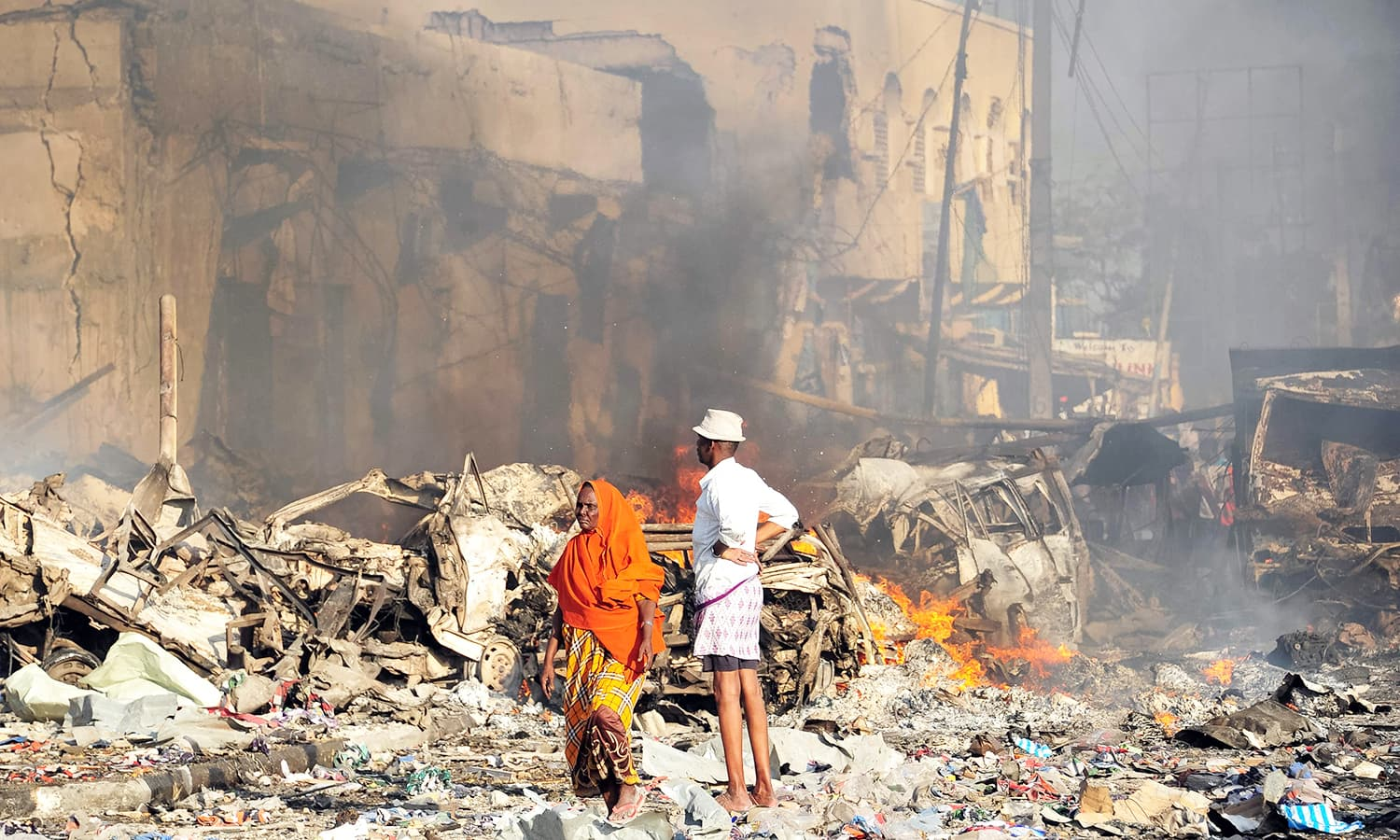 A man and woman look at the damages on the site of the explosion of a truck bomb in the centre of Mogadishu.─AFP