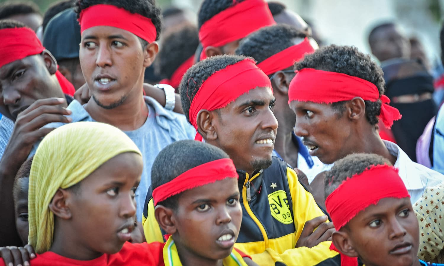 People wear red headbands as a sign of anger as they protest against the deadly bomb attack in Mogadishu .─AFP
