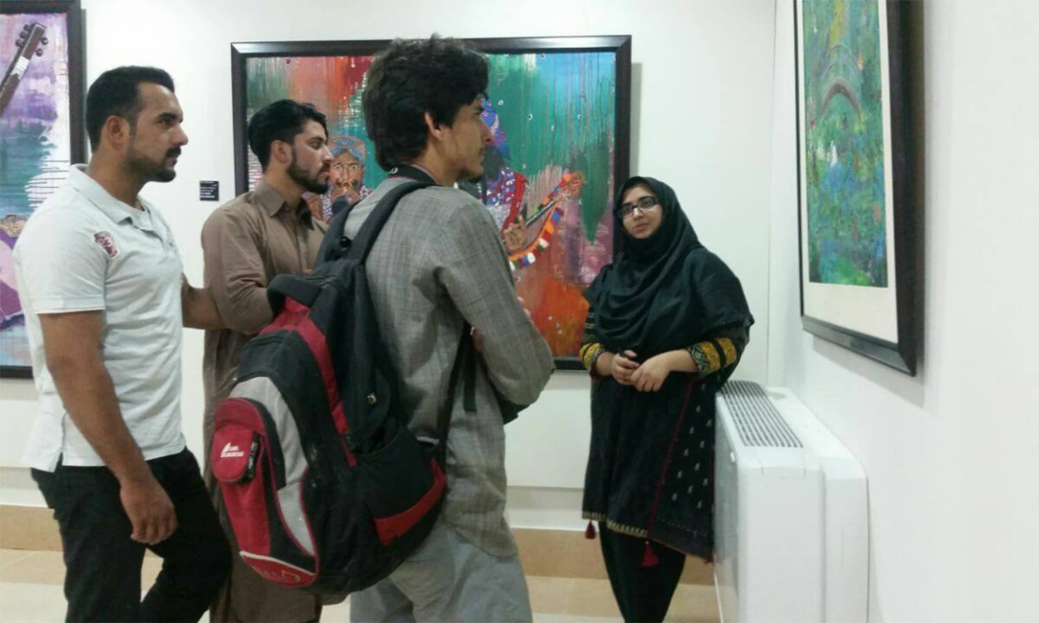 Artist Sana Gharshin speaks to visitors at her exhibition in Quetta.─Photo by author