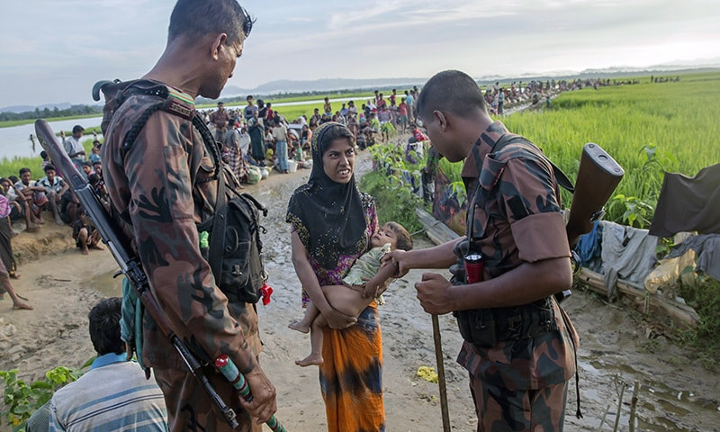 A newly arrived Rohingya woman holds her sick son as a Bangladesh border guard soldier checks him before allowing them to proceed forward to receive medical assistance.—AP